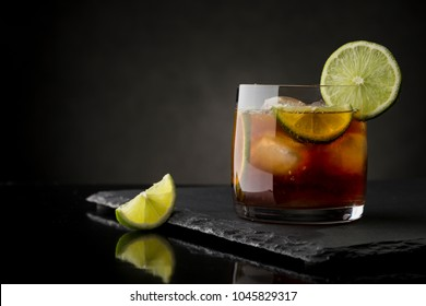 Cuba Libre cocktail with brown rum, lemon juice, coke and ice cubes, decorated with fresh lime slice on modern black stone tray