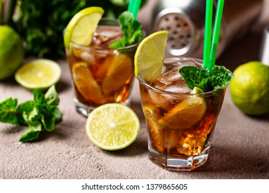Cuba libre cocktail with mint, lime and ice