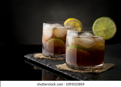 Cuba Libre cocktails with brown rum, lemon juice, coke and ice cubes, decorated with fresh lime slice on modern black stone tray