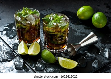 Cuba libre cool cocktail of cola, rum,  lime, mint and soda, in  glass with ice, holidays party concept
