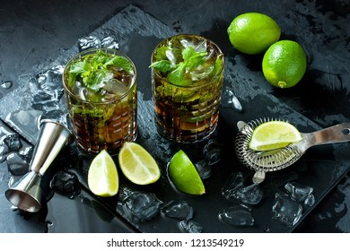 Cuba Libre or iced tea cocktail with strong alcohol, cola, lime and ice, two glass, dark background  with copy space