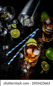 Cuba Libre, long island or iced tea cocktail with strong alcohol, cola, lime and ice, two glass, dark background copy space top view