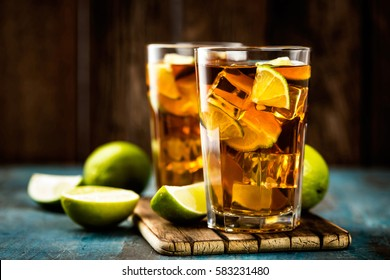 Cuba Libre or long island iced tea cocktail with strong drinks, cola, lime and ice in glass, cold longdrink or lemonade