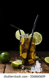 Cuba Libre longdrink with pieces of fresh lime and crushed ice on wooden background