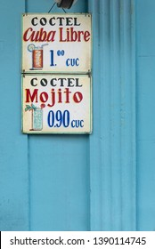 Cuba Libre and Mojito cocktails drink sign on blue wall background in Cuba.