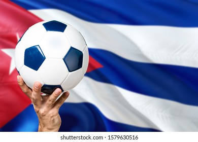 Cuba soccer concept. National team player hand holding soccer ball with country flag background. Copy space for text.
