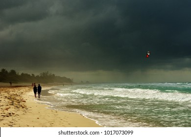 Cuba. Varadero beach with dark sky and couples walk on the beach before storm.