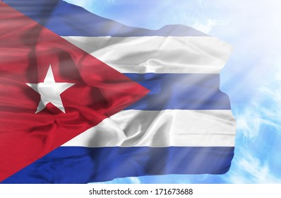 Cuba waving flag against blue sky with sunrays