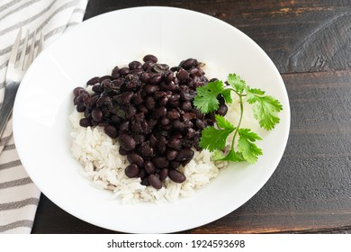 Cuban Black Beans (Frijoles Negros) Served Over White Rice: A plate of vegetarian beans and rice garnished with cilantro