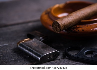 Cuban cigar in ashtray with lighter and cutter on rustic table