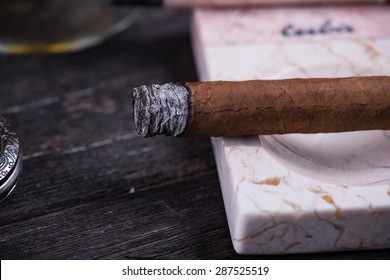 Cuban cigar in expensive marble ashtray on rustic table