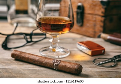 Cuban cigar and a glass of cognac brandy on wooden background, closeup view with details