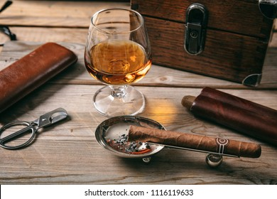 Cuban cigar and a glass of cognac brandy on wooden background, closeup view