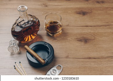 Cuban cigar on a black ceramic ashtray, a glass of bourbon whiskey with a whiskey decanter, a stainless steel cigar cutter and matches on the wooden table