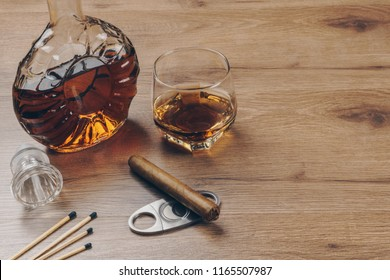 Cuban cigar on a stainless steel cigar cutter, a glass of bourbon whiskey with a whiskey decanter and matches on the wooden table