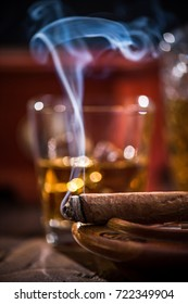 Cuban cigar smoke and luxurious Cognac in carafe.