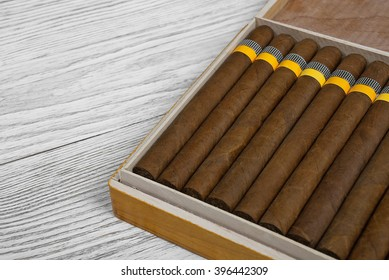 Cuban cigars in the cigar box on a light wooden background