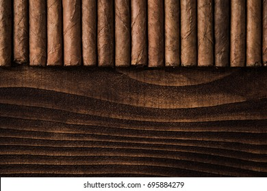 Cuban cigars close up on wooden table, border background. Directly from above top view