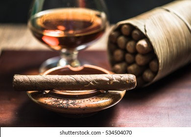 Cuban cigars and glass of alcohol on wooden desk