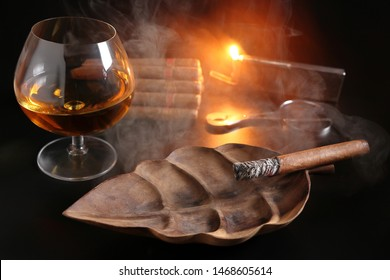 CUBAN CIGARS IGNITED IN A WOODEN ASHTRAY SURROUNDED BY CURLS OF SMOKE WITH A CIGAR CUTTER AND THE FLAME OF LIGHTER AND A SET OF CIGARS WITH A GLASS OF COGNAC