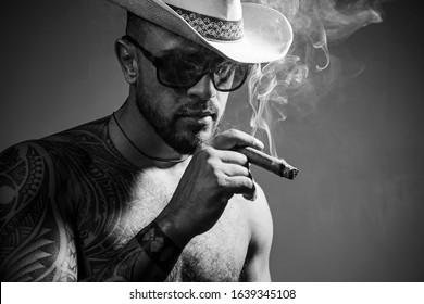 Cuban cigars. Portrait of latin face with a sensual look. Cuban man smoking cigar and enjoy life and moment. People concept. Time to enjoy