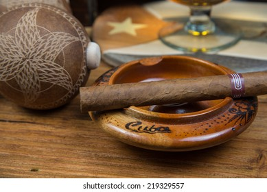 Cuban cigars and Rum or other alcohol in glass on table top view with vintage wooden background