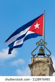 Cuban flag flies completely in blue sky with white fluffy clouds