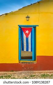 Cuban flag hanging down in door frame in Trinidad, Cuba