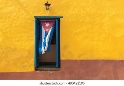 Cuban flag hanging on a door in Trinidad, Cuba