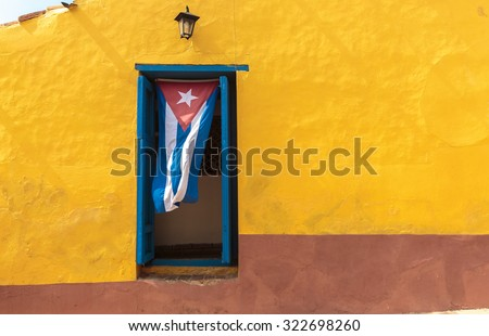 Cuban flag hanging on a door in Trinidad, Cuba