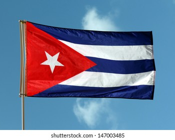 Cuban Flag On Flagpole Against Blue Sky With White Clouds