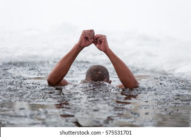 Cuban man swims in an ice hole in winter. Man is immersed in water