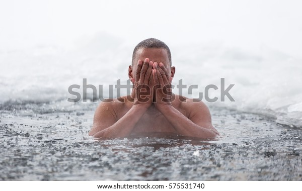 Cuban man swims in an ice hole in winter