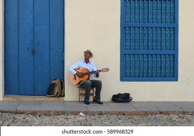 Cuban man wearing traditional panama straw hat playing an acoustic guitar. Taken in Trinidad, Cuba