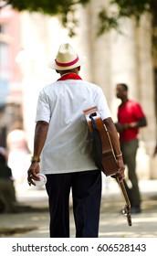 Cuban man wearing traditional panama straw hat playing an acoustic guitar. Cuba