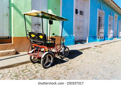 Cuban taxi bicycle parked in front of colorful colonial houses on Trinidad street