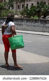 A Cuban woman standing by road, carrying green pocket after shopping in a local market.
