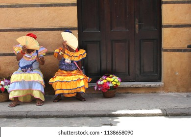 Cuban women in the national historic colored clothes with a fan