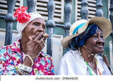 Cubans women smoking cigar and looking at camera