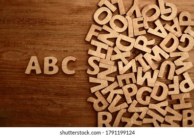 cube alphabets on a wooden surface. abc - letters.scattered mixed brown wooden letters of the English alphabet on white background, copy space, as a background composition