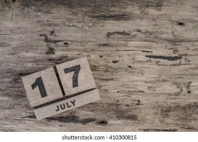cube calendar for july on wooden surface with copy space