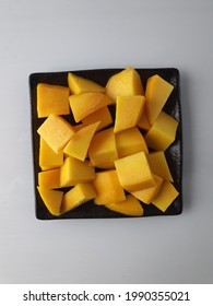 Cube cut R2E2 mango on square black ceramic plate. White grey background. A large mango with a good yellow sweet flavor with aroma when ripe. Fresh and juicy slice cut. Eaten raw.