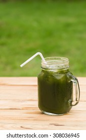 Cube glass with handle of rich cool Centella asiatica juice with white straw on the wooden table in green grass garden
