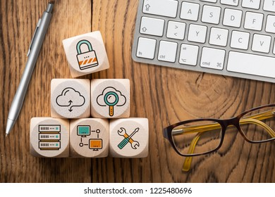 """cube with icons smybolizing """"cloud software"""" on wooden background"""