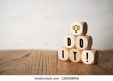 "cube with idea symbol and the message ""do it"" on wooden background"
