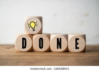 "cube with idea symbol and the message ""done"" on wooden background"
