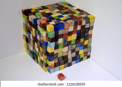 A cube made of colorful wood cubes, each cube is 1x1x1 centimeter, the wole cube consists of 1000 of such cubess, thus its volumen is 1000 cm^3 or one liter