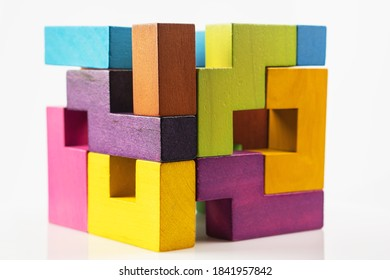 Cube made of multicolored wooden figures on a white background.