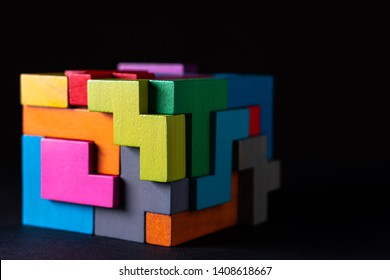 Cube made of multicolored wooden geometric shapes. Concept of decision making process, creative, logical thinking. Choose correct answer. Logical tasks. Conundrum.