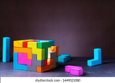 Cube of multi-colored wooden shapes. Concept of decision making process, creative, logical thinking. Choose correct answer. Logical tasks. Conundrum, find the missing piece of the proposed.